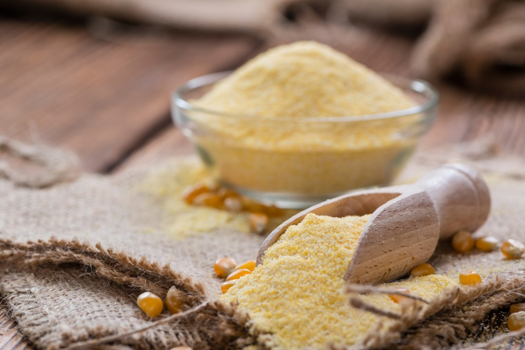 Portion of fresh Cornmeal (close-up shot) on rustic wooden background