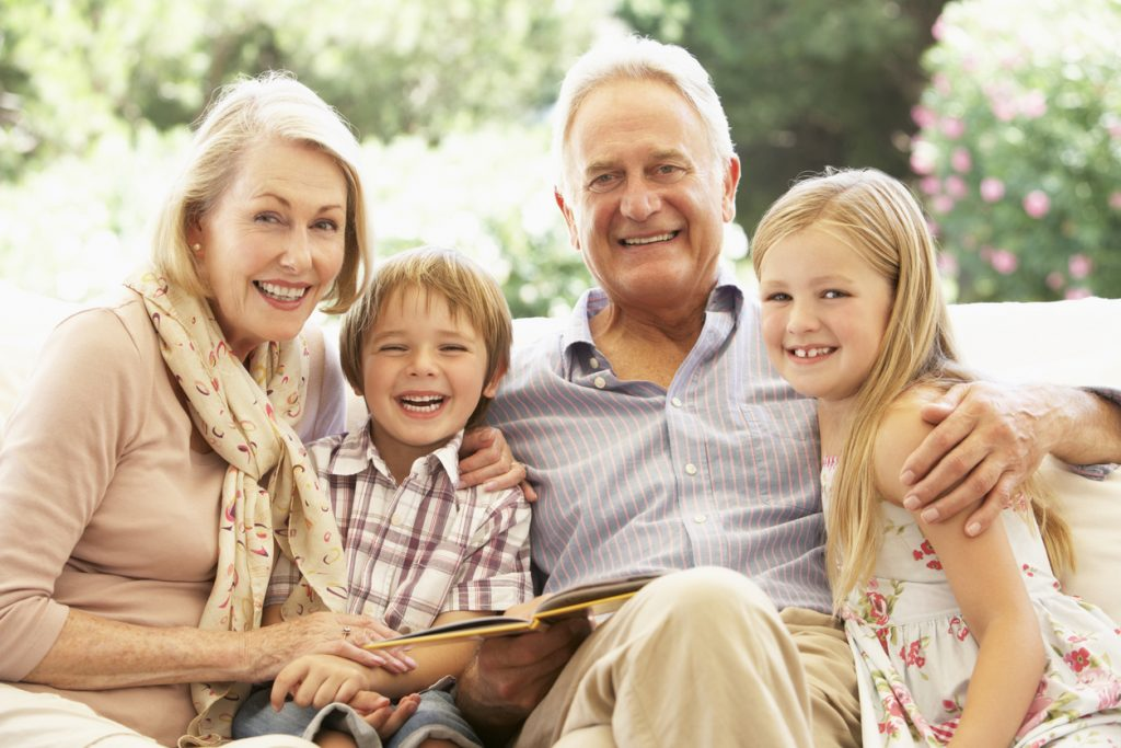 Portrait Of Grandparents Reading To Grandchildren On Sofa Smiling to Camera
