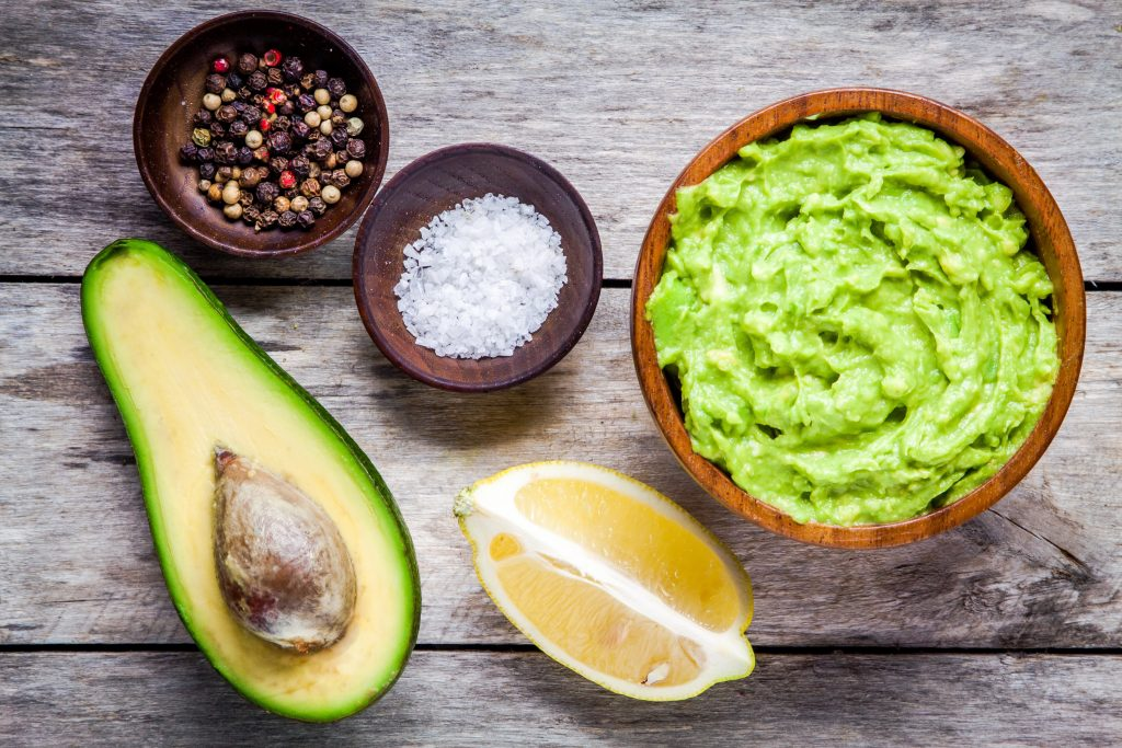 ingredients for homemade guacamole: avocado, lemon, salt and pepper top view